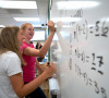 Sophomores work out math problems on the whiteboard
