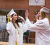 Students high five on caps and gowns on Graduation Day