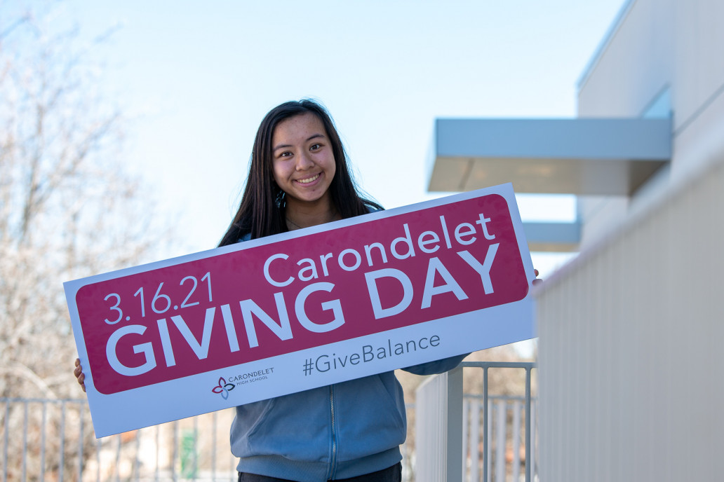 Maddie Wu '21 holds a Giving Day sign