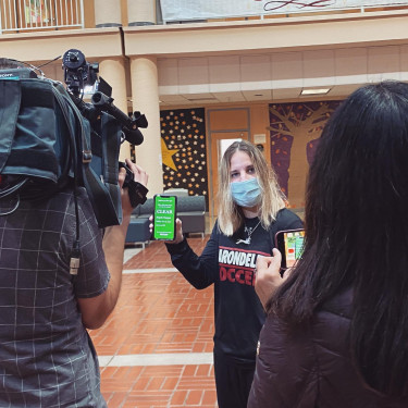 "Angela Napper '22 shows off the green ""Clear"" screen to the NBC Bay Area news crew for a re..."