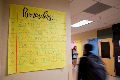 A handwritten sign promoting self-care and positive attitudes hanging in a busy hallway.