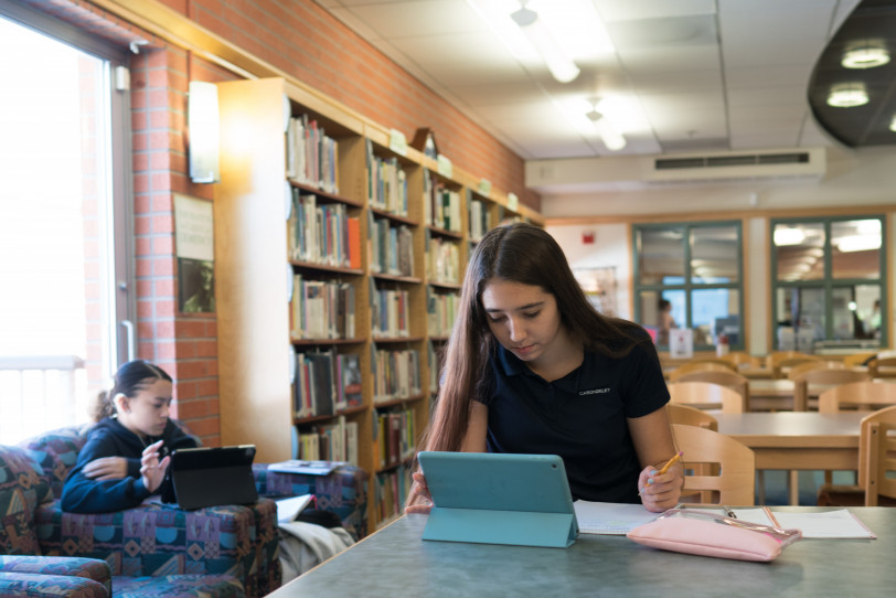 Two students work on their individual iPads in the library